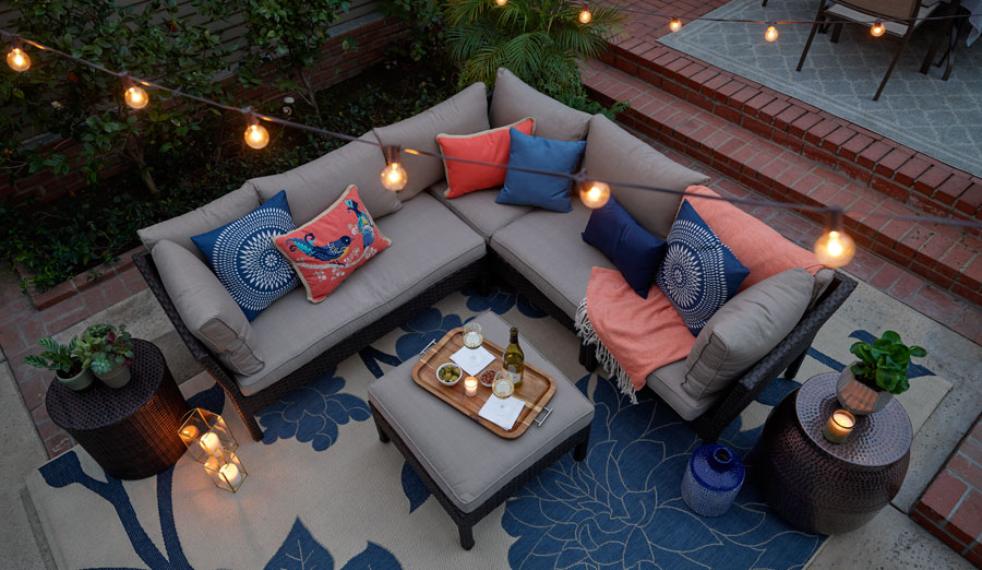 Overhead shot of outdoor conversational set with floral outdoor rug, throw pillows, throw and string lights