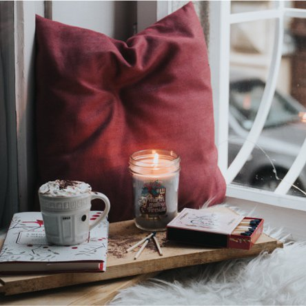 A reading nook styled next to a window with a faux fur throw, plump red pillow, hot chocolate and a book on a wooden tray with a candle. Links to a blog post about what is hygge and how to bring the happy Danish way of living home.