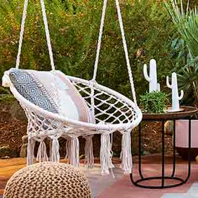 A woven hanging egg chair. Links to where to shop bohemian outdoor furniture and decor.