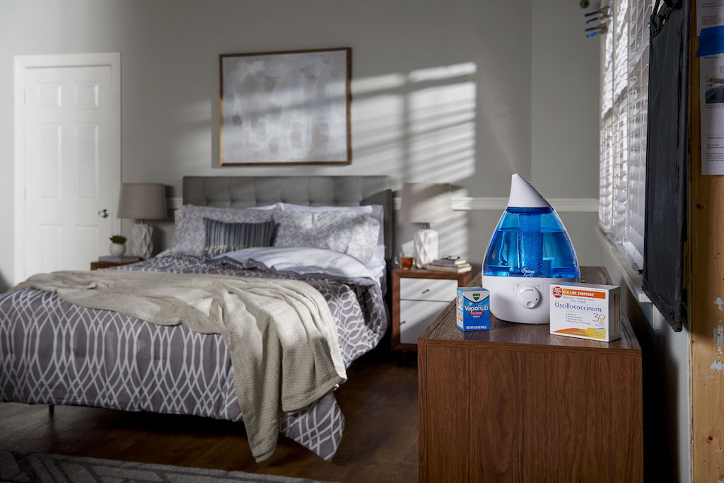 bedroom with humidifier and medicine on nightstand