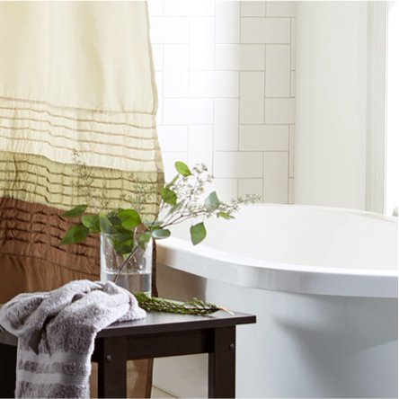 A master bathroom decorated in the traditional style with a brown shower curtain, bath tub, and a house plant on a wooden stool. Links to a blog post about how to waste less at home and live more sustainably.
