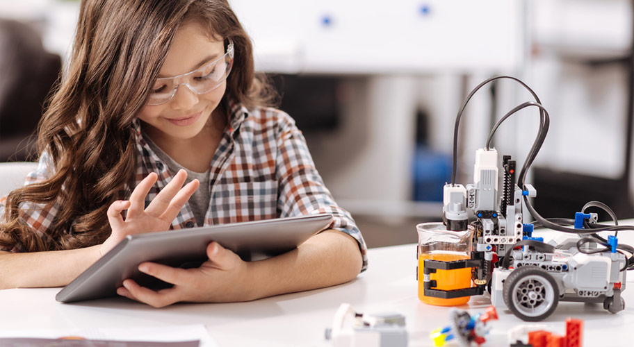 Image of a young girl with a tablet working on an engineering project