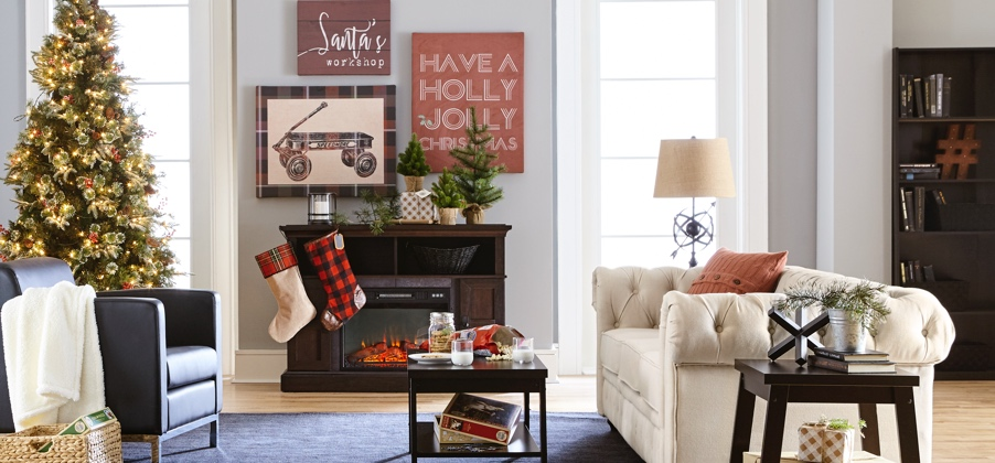A cozy transitional style living room with a tufted sofa, blue armchair and electric fireplace with stockings hung in front and a Christmas tree to the side. Links to a post about how to maximize light during winter months.