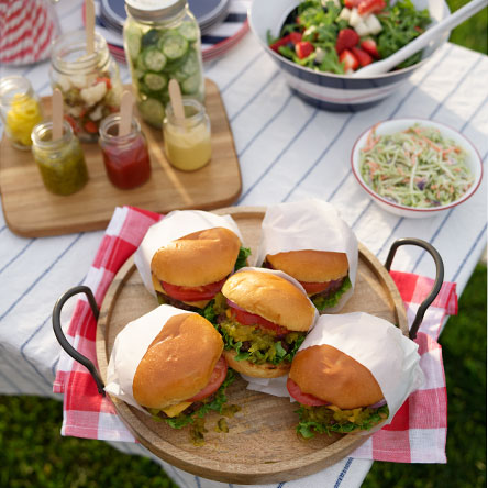 Close up of burgers with all the fixings on a platter on an outdoor table