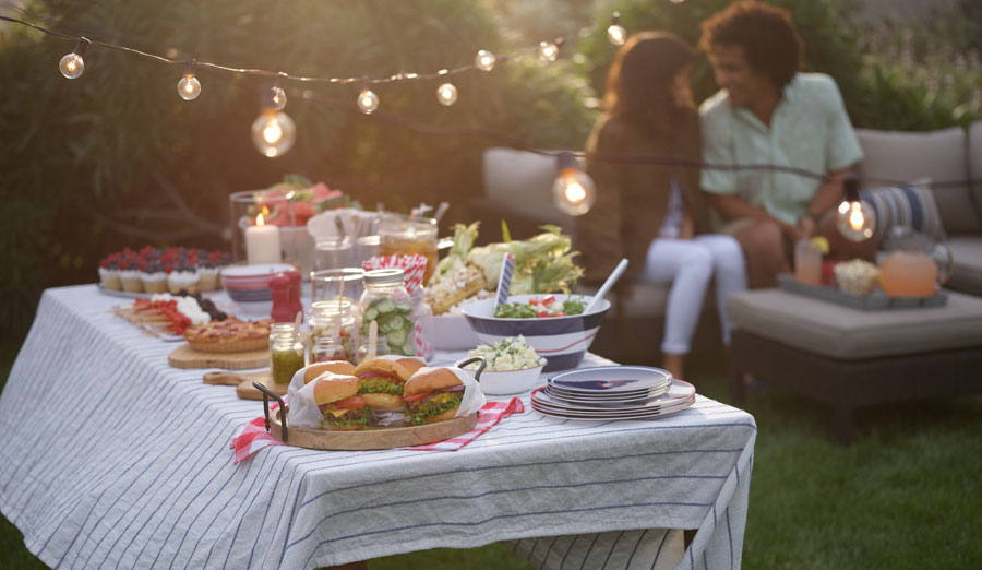 Outdoor dining table set with 4th of july picnic foods at dusk with string lights hanging above