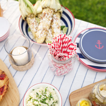Side dishes such as potato salad and grilled corn on outdoor table