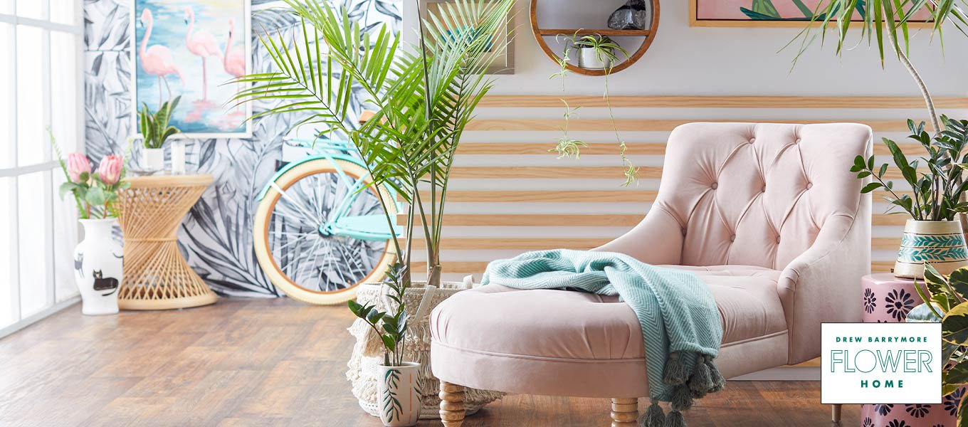 Shop Bungalow Vibes by Drew Barrymore Flower Home. A bohemian nook with a light pink chaise lounge and natural elements.