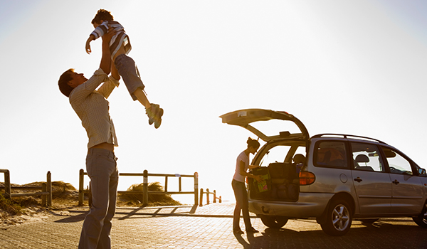 father lifting up his child in the air during a bread on a family road trip with mom in the background next to the family car