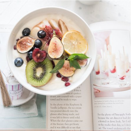 A white bowl filled with oatmeal topped with fresh fruit and an open book with healthy recipes inside. Links to a blog post about the affordable finds that are the secret to keeping your new years health resolutions.