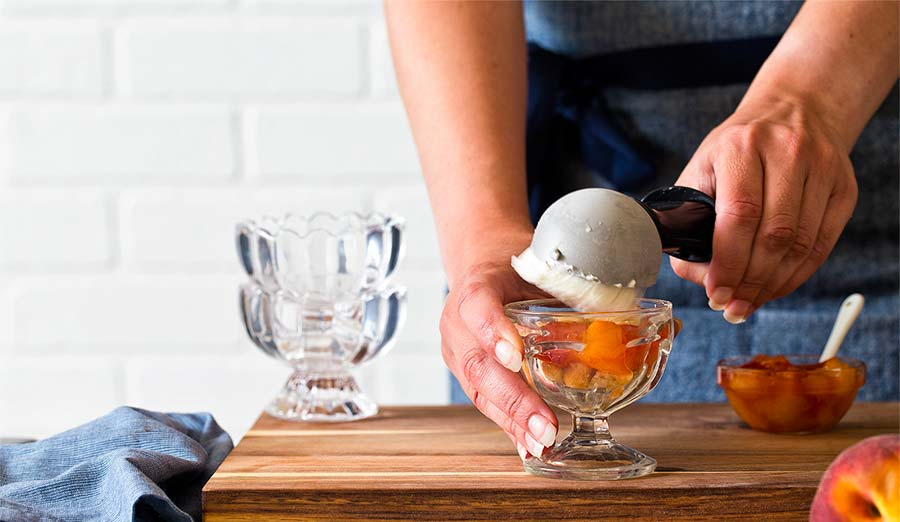 adding ice cream to sundae over peaches
