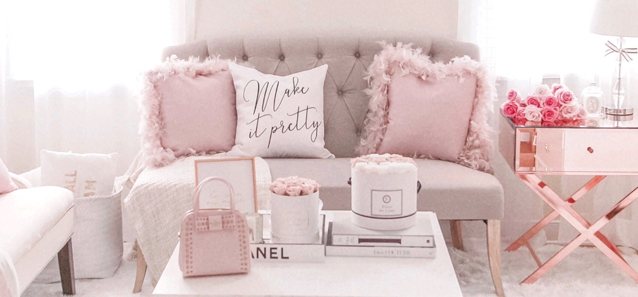 A glam style living room with a tufted loveseat, feminine decorative pillows and a mirrored accent table. Links to a blog post about jadore Lexie Couture's glam, kid-friendly style.