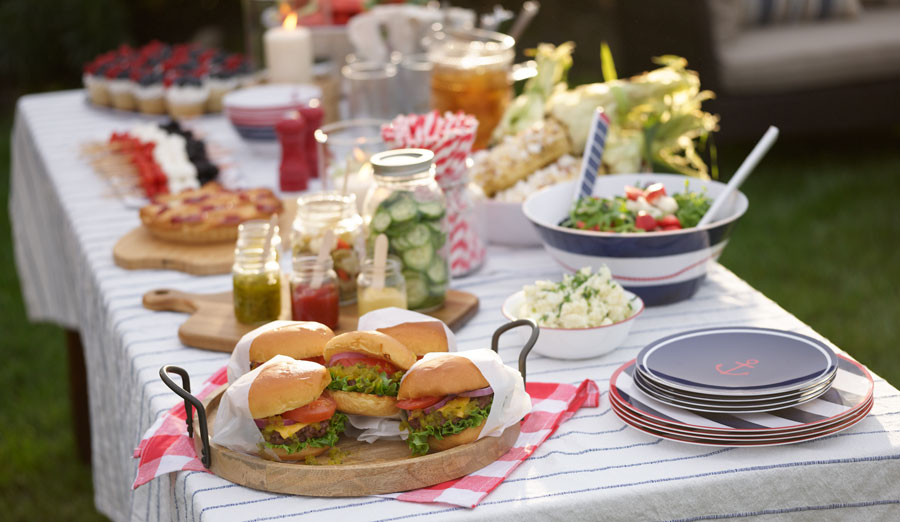 Closeup of outdoor dining table with white tablecloth, red, white and blue melamine plates, and summer food dishes such as burgers, salads and toppings