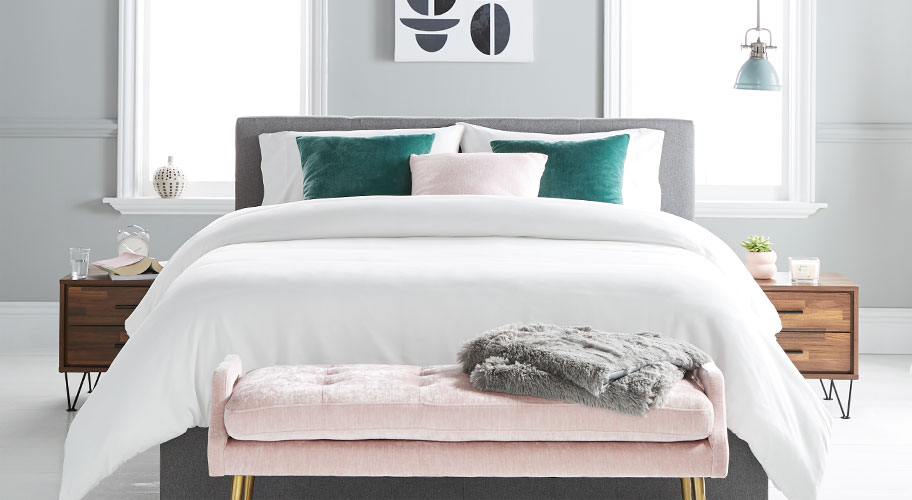 A bedroom styled with a gray upholstered mid-century style bed, two wooden mid-century style nightstands and a pink velvet upholstered bench and velvet decorative pillows. Links to where to buy luxury mid-century modern bedroom furniture and decor