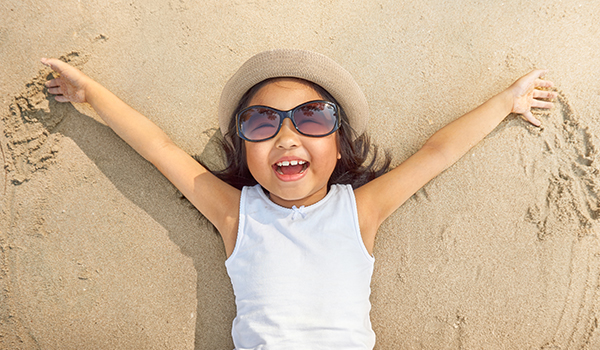 young girl in sunglasses lying in the sand on a beach, making sand angels with her arms and smiling