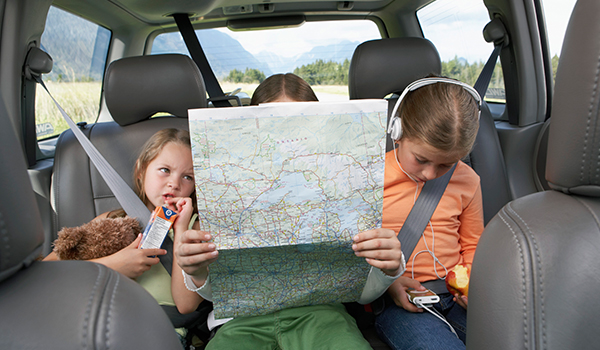 3 young kids in the back seat of the car reading a map and listening to music