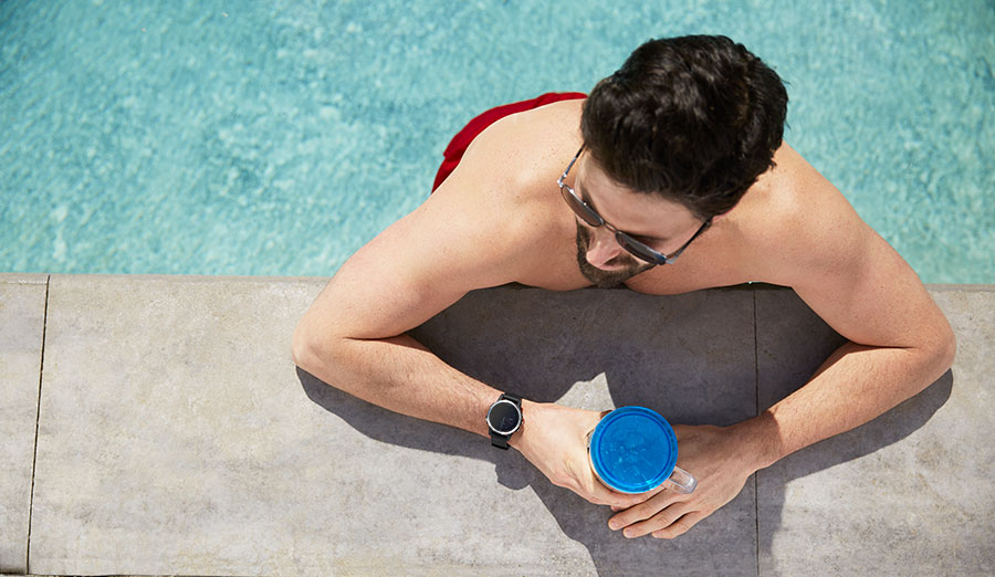 Guy in swim shorts leaning on the edge of the pool wearing a smartwatch and holding a drink