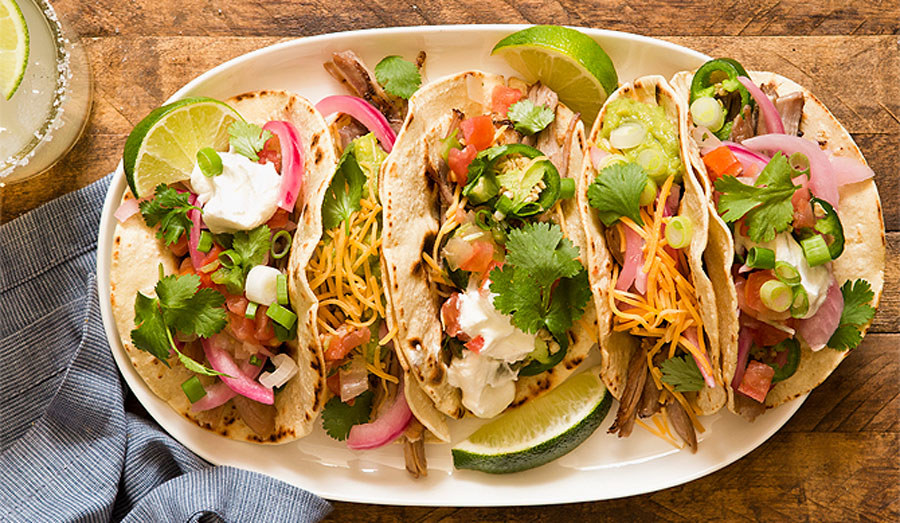 Top view of 5 tacos on a plate