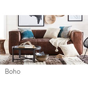 A boho style living room with a leather sofa, woven accent chair, eclectic area rug and gallery wall. Links to where to shop for boho style living room furniture and decor.
